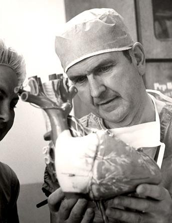 Russell M. Nelson explica um procedimento cirúrgico para uma enfermeira.