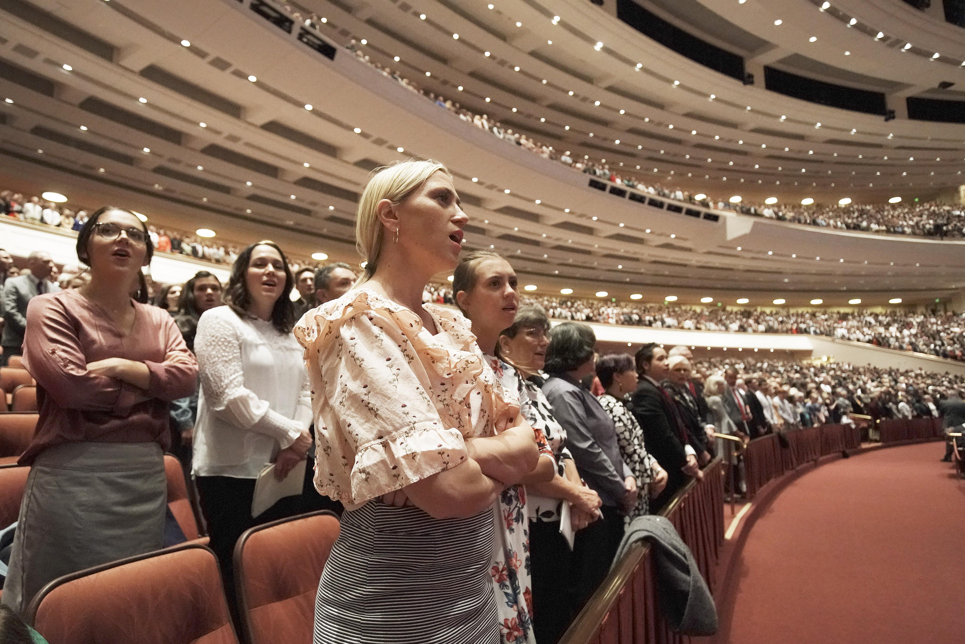 Julie Beck canta com outros membros da congregação presentes na conferência durante a sessão da manhã de sábado da Conferência Geral Semestral nº 189 de A Igreja de Jesus Cristo dos Santos dos Últimos Dias, realizada no Centro de Conferências em Salt Lake City, Utah, EUA, em 5 de outubro de 2019.