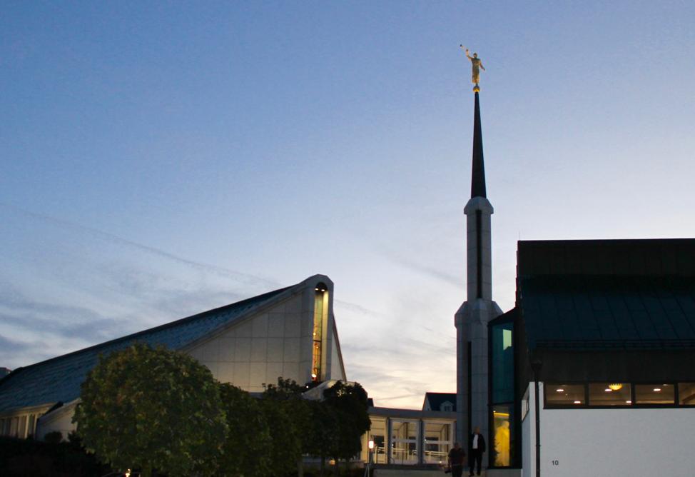 O pináculo, a frente e a praça de entrada do Templo de Frankfurt Alemanha no crepúsculo do dia 18 de outubro, 2019. Um reflexo da estátua do Cristo dentro do anexo é visível na janela abaixo à direita.