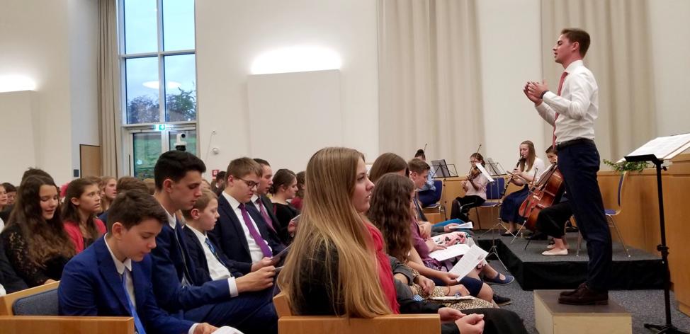 """A congregação junta-se a um pequeno grupo orquestral e ao coro cantando """"As Famílias Poderão Ser Eternas"""" no devocional para os jovens em Friedrichsdorf, Alemanha, em 19 de outubro de 2019, véspera da rededicação do Templo de Frankfurt."""