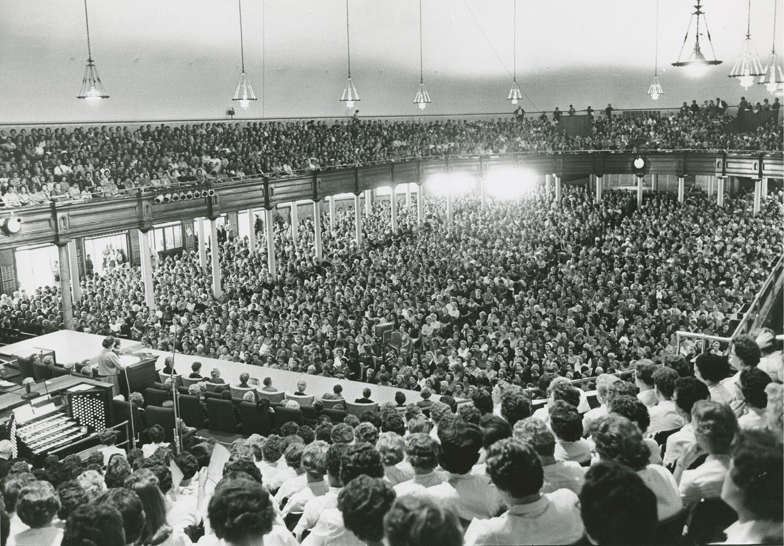 Conferência geral da Sociedade de Socorro em 1962. A primeira conferência geral da Sociedade de Socorro aconteceu em 1889. Essa fotografia do Tabernáculo de Salt Lake mostra uma grande multidão em uma das sessões da conferência de outubro de 1962, em que irmã Louise W. Madsen discursou. Fotografia de Ross Welser.