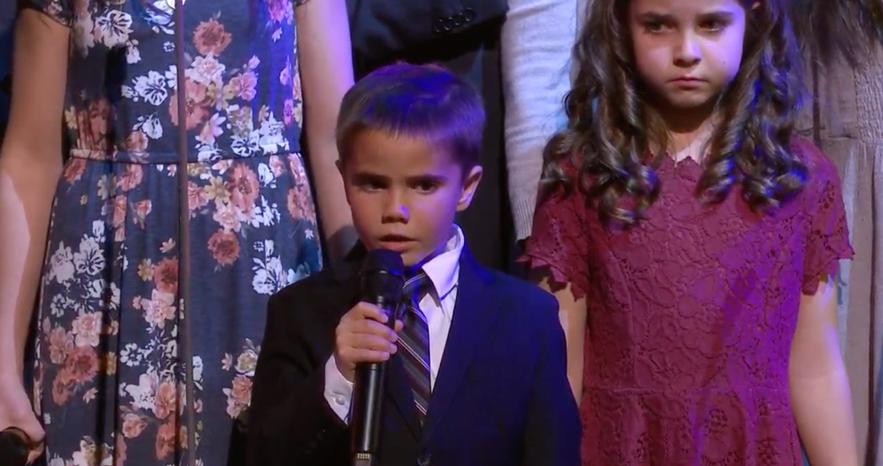 Uma criancinha canta o novo hino da Primária com sua família durante um evento Cara a Cara sobre o programa para Crianças e Jovens no Tabernáculo em Salt Lake City, no dia 17 de novembro.