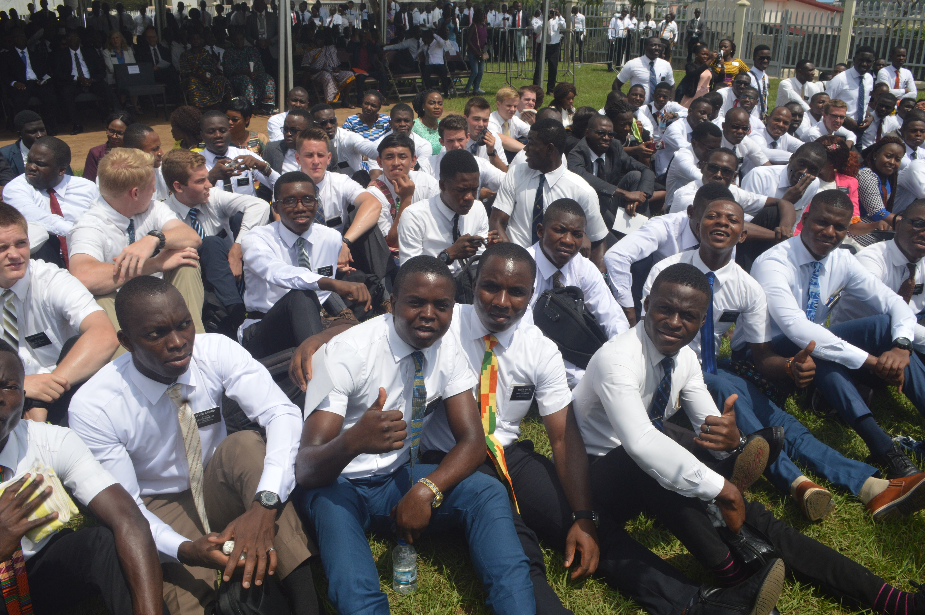 Convidados pelo élder Neil L. Andersen para se aproximarem da cerimônia de abertura de terra, os missionários se reúnem no futuro local do Templo de Abidjan Costa do Marfim em 8 de novembro de 2018.