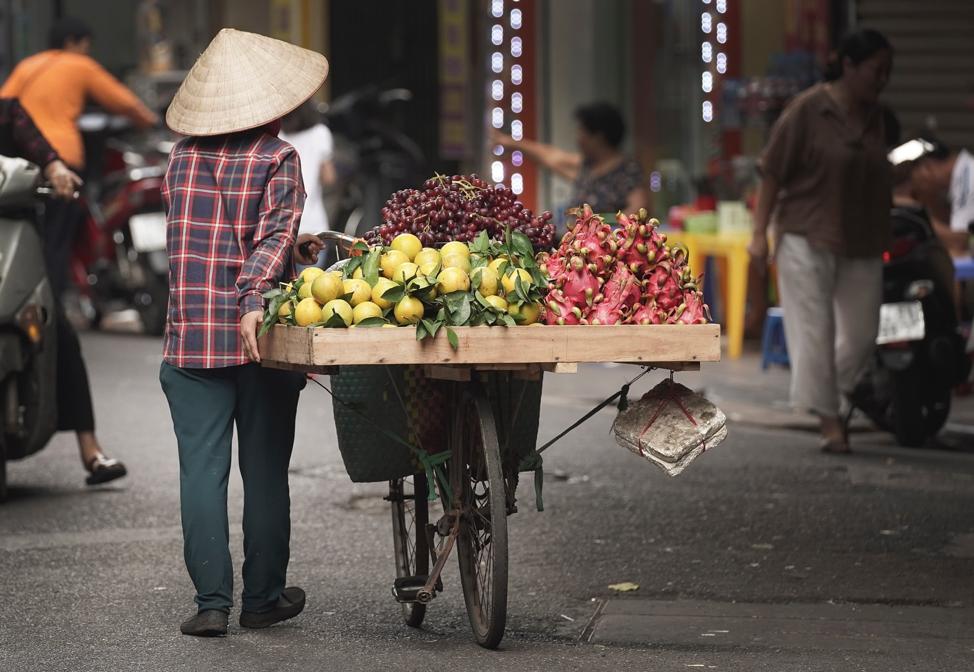 Uma mulher vende produtos em Hanói, Vietnã, no domingo, dia 17 de novembro, 2019.