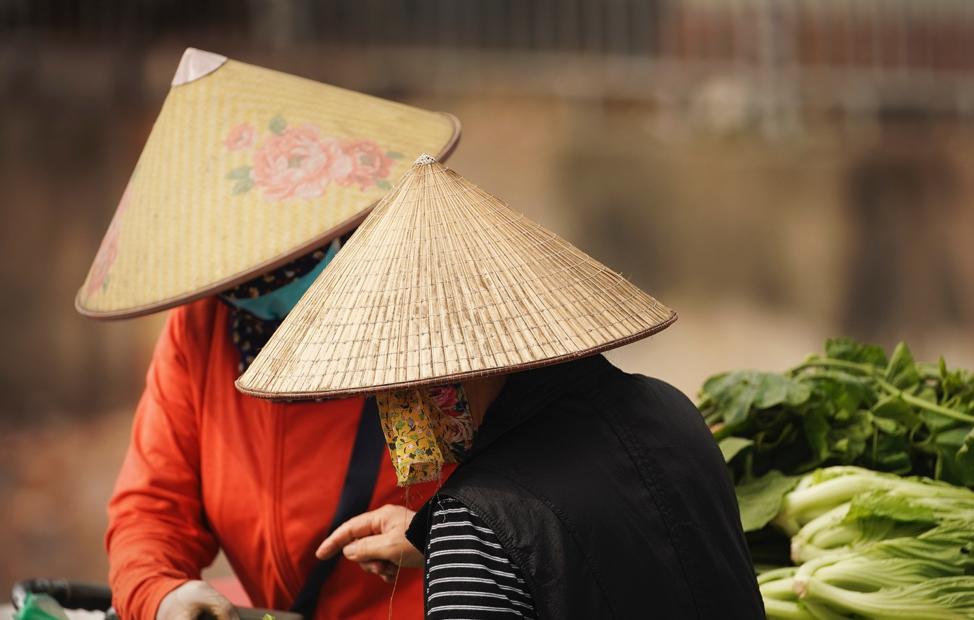 Mulheres vendem produtos na rua em Hanói, Vietnã, no sábado, dia 16 de novembro, 2019.
