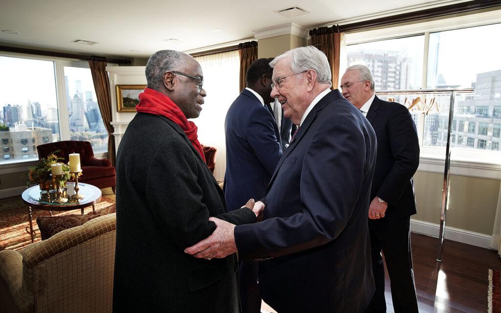 O presidente M. Russell Ballard, presidente interino do Quórum dos Doze Apóstolos de A Igreja de Jesus Cristo dos Santos dos Últimos Dias, à direita, cumprimenta Koné Tanou, observador permanente das Nações Unidas da Comunidade Econômica dos Estados da África Ocidental, em Nova York no sábado, 16 de novembro de 2019. Atrás, à direita, o élder Jack N. Gerard, setenta autoridade geral, cumprimenta Abdou Abarry, embaixador da ONU do Níger.