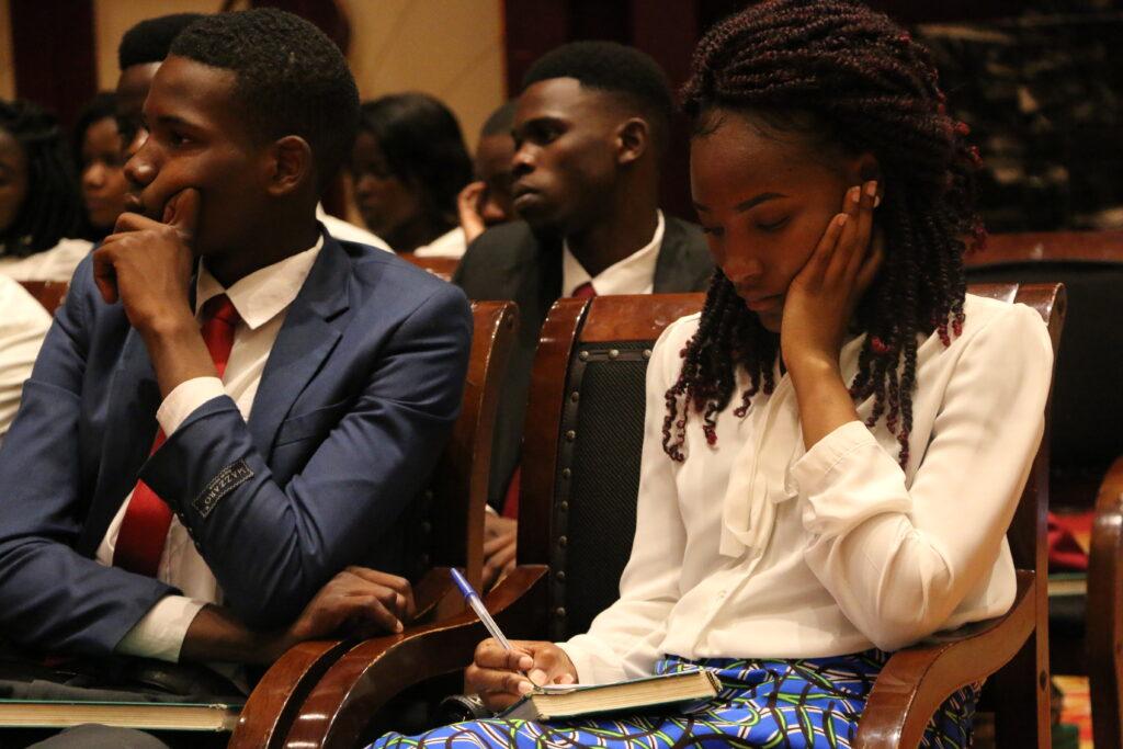 Jovens adultos escutam e fazem anotações enquanto élder Jeffrey R. Holland, do Quórum dos Doze Apóstolos, fala durante uma conferência multi-estacas no Centro de Conferências Joaquim Chissano Internacional em Maputo, Moçambique, no domingo, dia 17 de novembro, 2019.