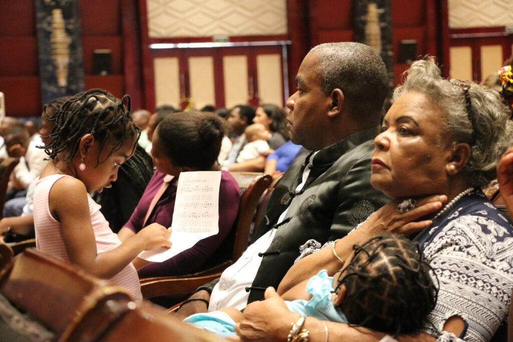 Uma família escuta ao élder Jeffrey R. Holland, do Quórum dos Doze Apóstolos, falando durante uma conferência multi-estacas no Centro de Conferências Joaquim Chissano Internacional em Maputo, Moçambique, no domingo, dia 17 de novembro, 2019.