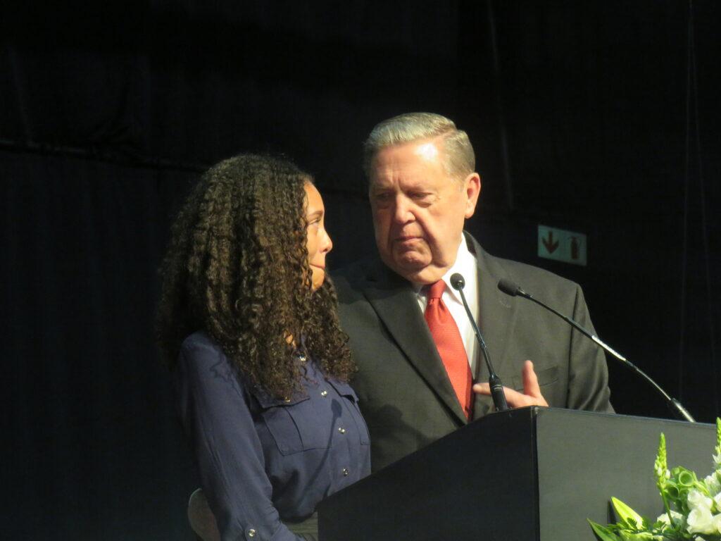 Élder Jeffrey R. Holland, do Quórum dos Doze Apóstolos, de pé próximo a Judith Mahlangu, uma missionária recém retornada, ao púlpito durante uma conferência multi-estacas no Centro de Convenções Gallagher perto de Johanesburgo, África do Sul, no domingo, dia 10 de novembro, 2019.
