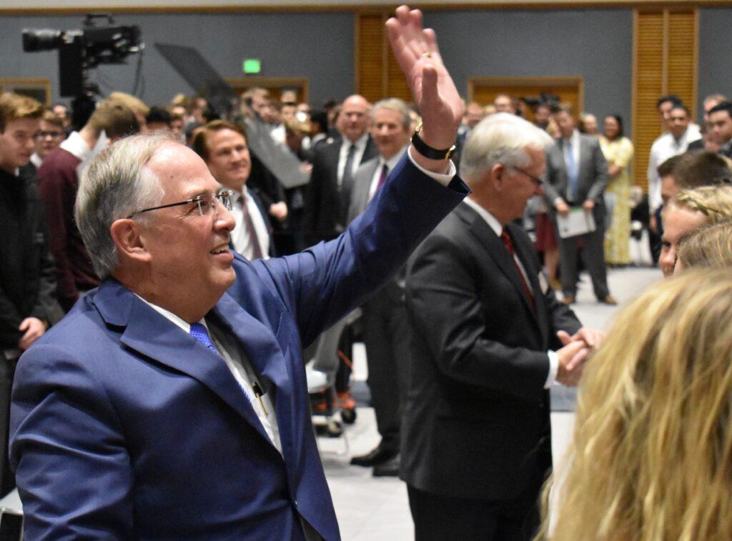 Élder Neil L. Andersen, do Quórum dos Doze Apóstolos, acena para missionários sentados em cima no auditório após um devocional do Dia de Ação de Graças no Centro de Treinamento Missionário de Provo no dia 28 de novembro, 2019, em Provo, Utah.