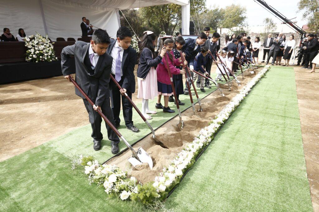 Crianças Santos dos Últimos Dias levantam pá cheia de terra na abertura de terra do Templo de Puebla México, no sábado, dia 30 de novembro, 2019.