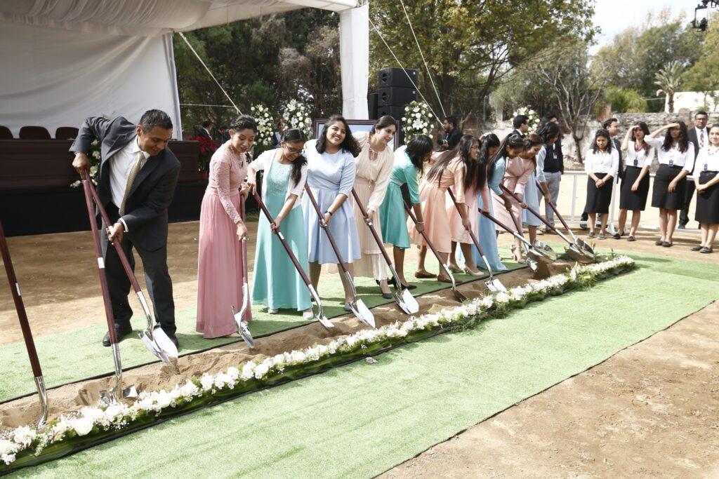 Moças de A Igreja de Jesus Cristo dos Santos dos Últimos Dias usam pás para levantar terra na abertura de terra do Templo de Puebla México, no sábado, dia 30 de novembro, 2019.
