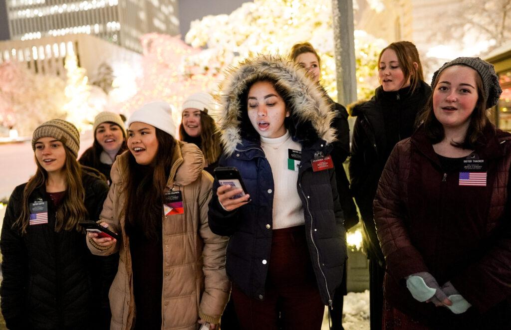Missionárias de A Igreja de Jesus Cristo dos Santos dos Últimos Dias cantam canções de Natal enquanto as pessoas desfrutam da primeira noite da exposição anual de luzes de Natal na Praça do Templo em Salt Lake City, Utah, na sexta-feira, 29 de novembro de 2019.