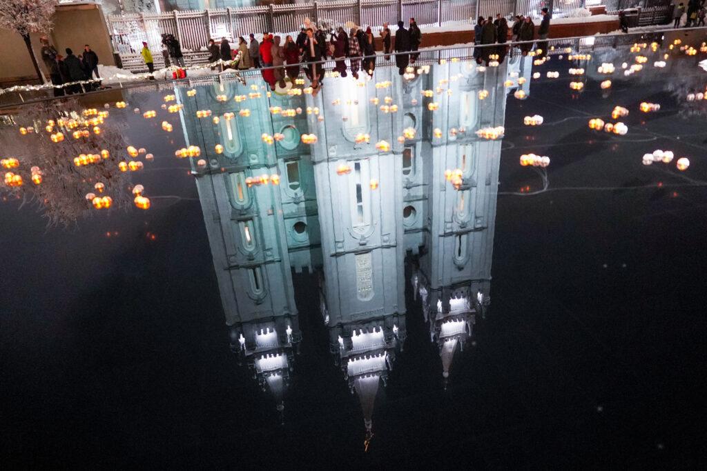 O Templo de Salt Lake de A Igreja de Jesus Cristo dos Santos dos Últimos Dias é visto no espelho d'água enquanto as pessoas apreciam a primeira noite da exposição anual de luzes de Natal na Praça do Templo em Salt Lake City na sexta-feira, 29 de novembro de 2019.