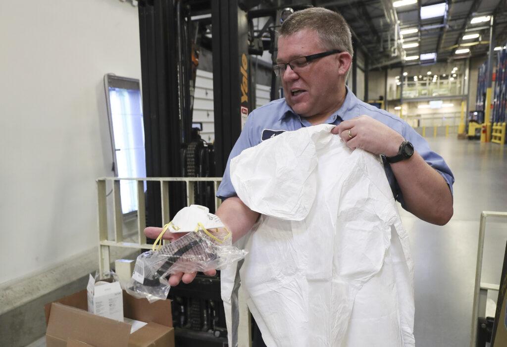 Adam Hunt, funcionário do armazém em Salt Lake City, segura uma máscara de respiração e óculos e traje de proteção conforme A Igreja de Jesus Cristo dos Santos dos Últimos Dias contribui enviando ajuda à China na quarta-feira, dia 29 de janeiro, 2020.