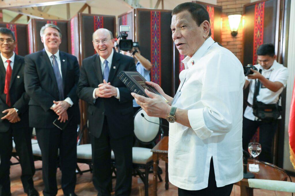 O Presidente das Filipinas, Rodrigo Roa Duterte, recebe uma cópia personalizada do Livro de Mórmon durante uma visita do Élder Quentin L. Cook em Manila, no dia 15 de janeiro, 2020.