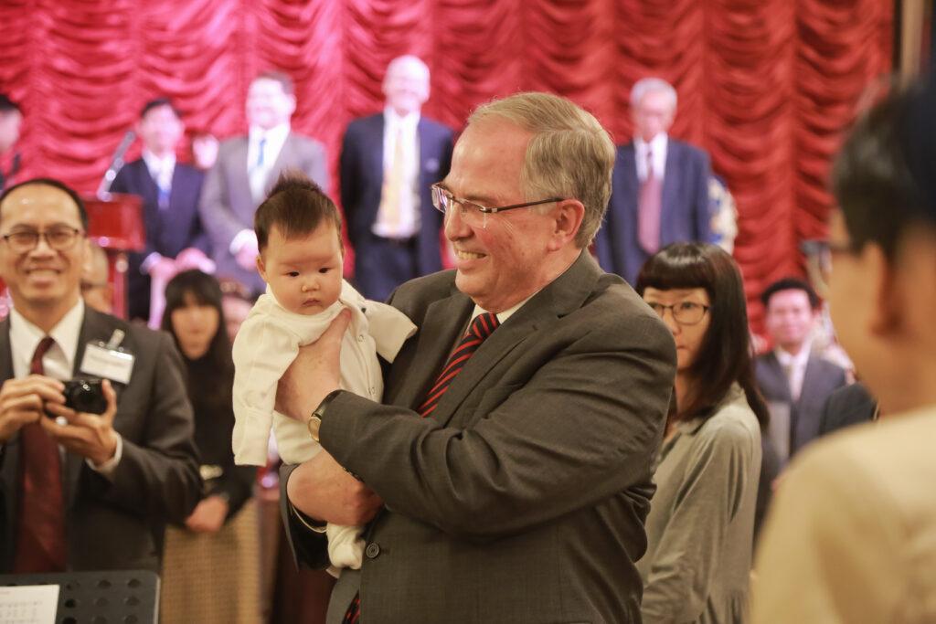 O Élder Neil L. Andersen segura uma criança durante uma reunião com os membros em Bangcoc, Tailândia, no dia 12 de janeiro de 2020.