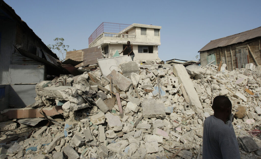 Um transeunte cobre sua boca por causa da poeira, ao andar em Porto Príncipe, Haiti, no dia 19 de janeiro, 2010 — uma semana depois que o terremoto de magnitude 7,0 atingiu a região.