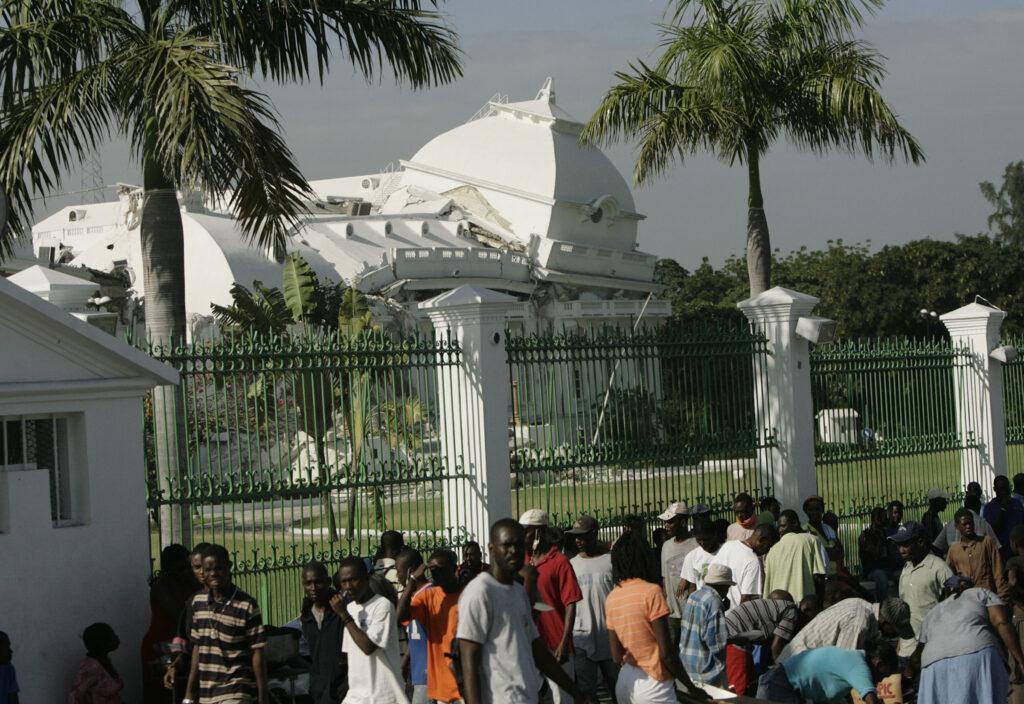 Os haitianos ficam em fila para pegar suprimentos perto da Catedral Nacional, parcialmente destruída, em Porto Príncipe, Haiti, no dia 19 de janeiro, 2010 — uma semana depois que o terremoto de magnitude 7,0 atingiu a região.