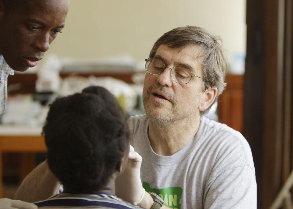 O Dr. Mark Rampton cuida do paciente Loubens Pierre, enquanto sua mãe, Renette Charles, permanece perto da capela da Ala Croix-des-Missions de A Igreja de Jesus Cristo dos Santos dos Últimos Dias em Porto Príncipe, Haiti, no dia 25 de janeiro, 2010.