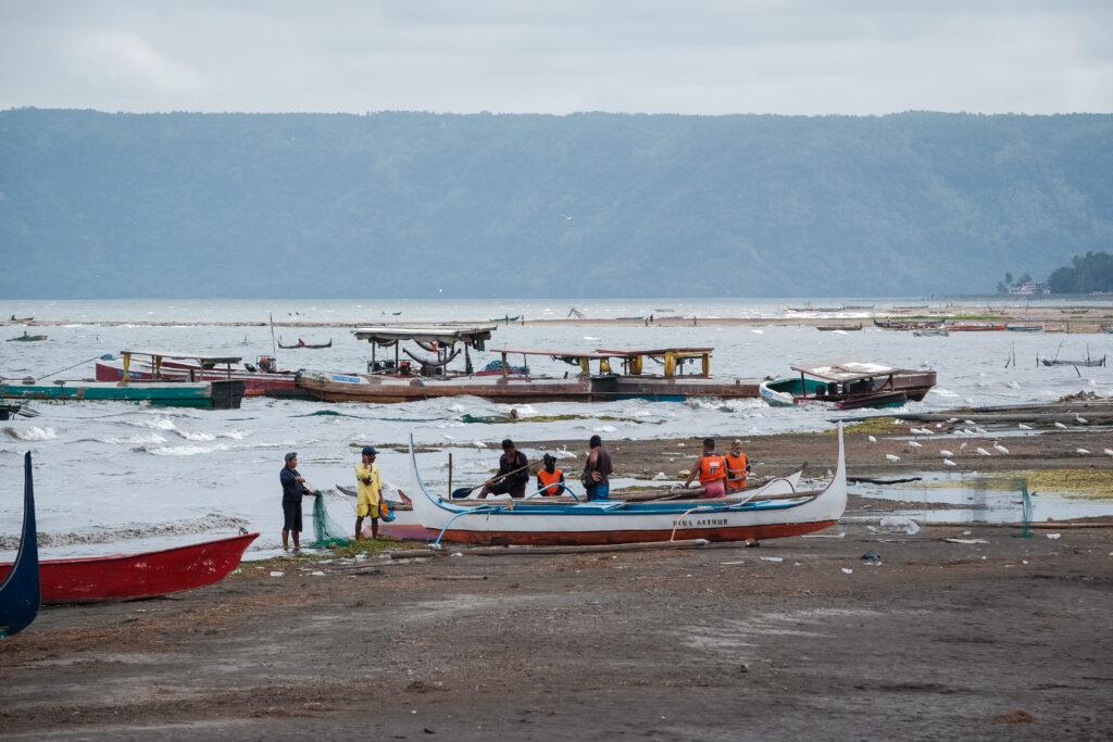 As pessoas que evacuaram das áreas circunvizinhas ao vulcão Taal retornam às margens do Lago Taal para fazer uma limpeza na quinta-feira, 6 de fevereiro de 2020, depois de serem impedidas de acessar a área por quase três semanas após as erupções vulcânicas.