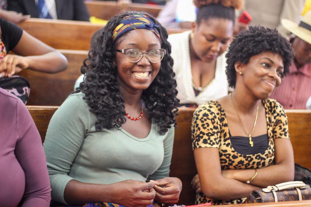 Membros em Mandeville, Jamaica, sorriem durante a transmissão de uma conferência de estaca especial com o Élder Dale G. Renlund no dia 23 de fevereiro, 2020. A conferência foi parte da avaliação anual da Área Caribe.