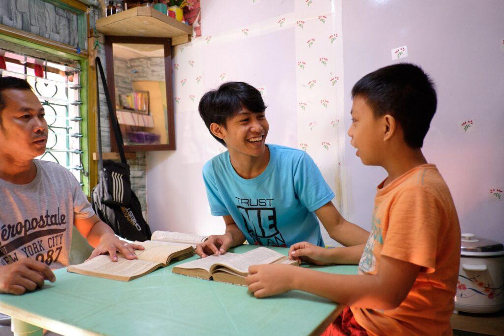 Rendelle Joshua Manguba, de Manila, nas Filipinas, lê um livro com seu pai e seu irmão mais novo. Os Serviços de Caridade Santos dos Últimos Dias fizeram parceria com o Caritas Manila, um programa católico de assistência social, durante a campanha #SejaALuzDoMundo a fim de financiar oportunidades educacionais para crianças em idade escolar.