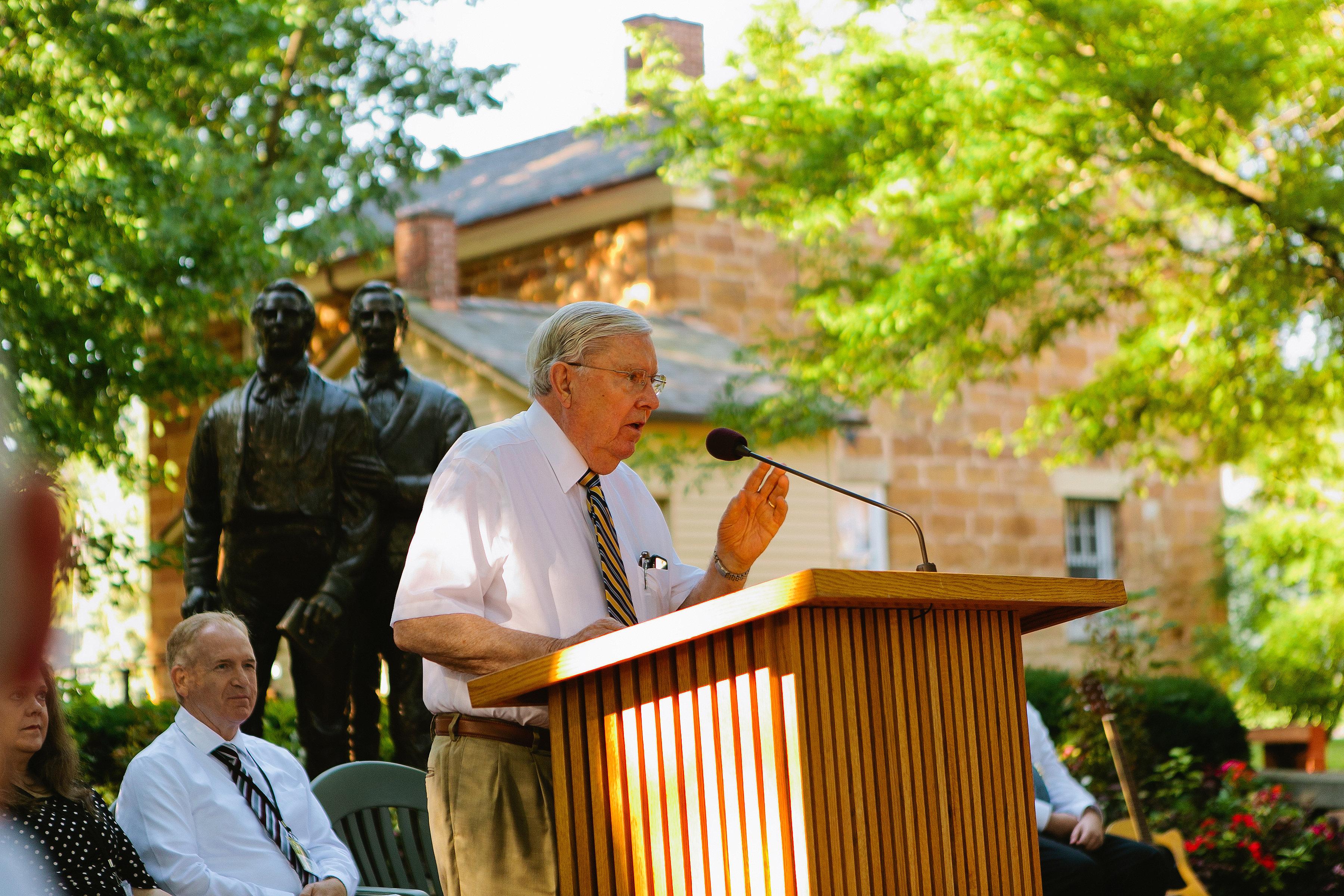 El élder M. Russell Ballard discursa en un devocional que se lleva a cabo afuera de la cárcel de Carthage el 5 de ago. El devocional conmemoró el aniversario número 25 de la dedicación del cementerio de la familia Smith.
