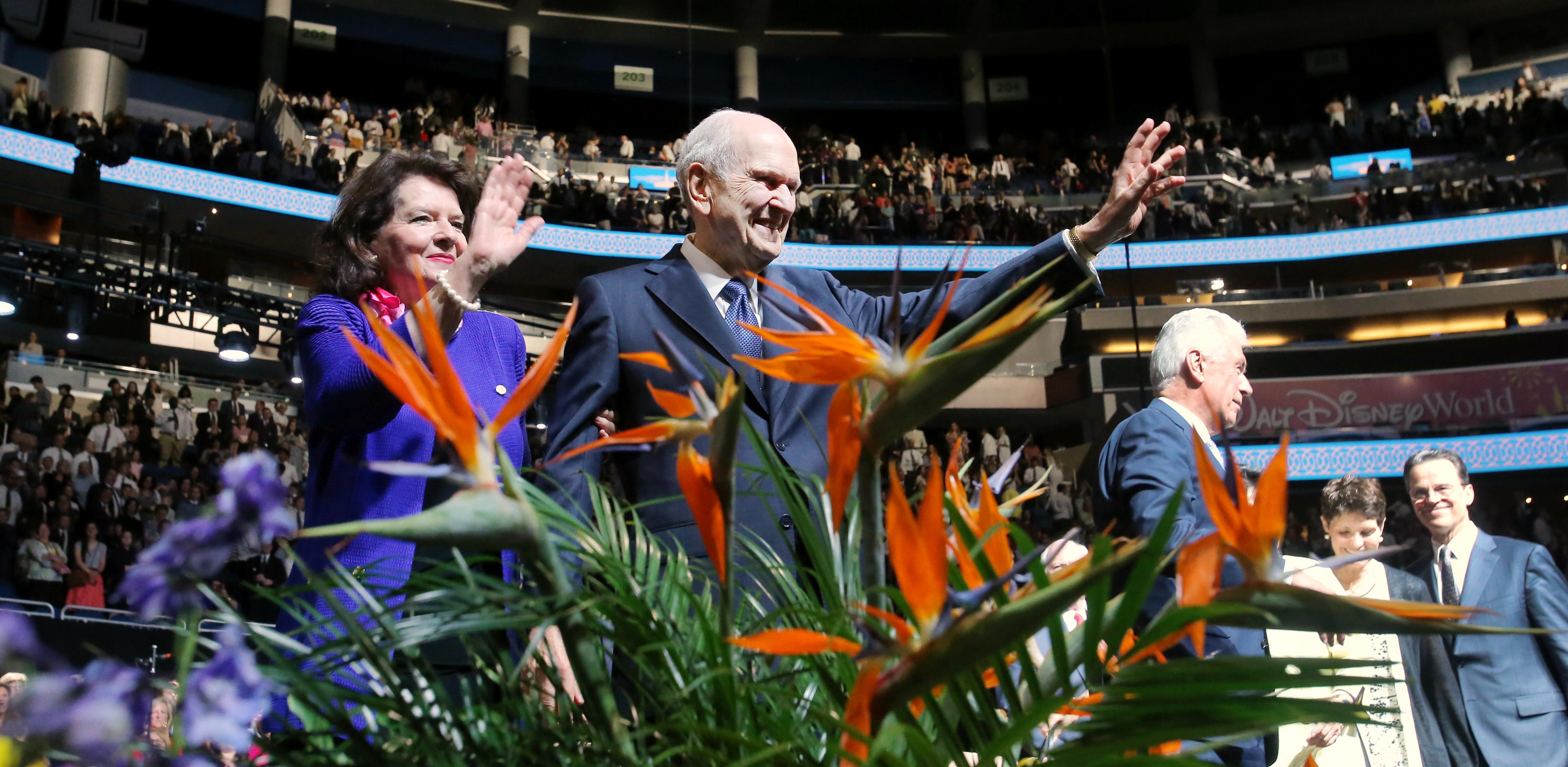 El presidente Russell M. Nelson y su esposa, la hermana Wendy Nelson, sonríen y saludan a los asistentes al Centro Amway después del devocional del 9 de junio de 2019 en Orlando, Florida.