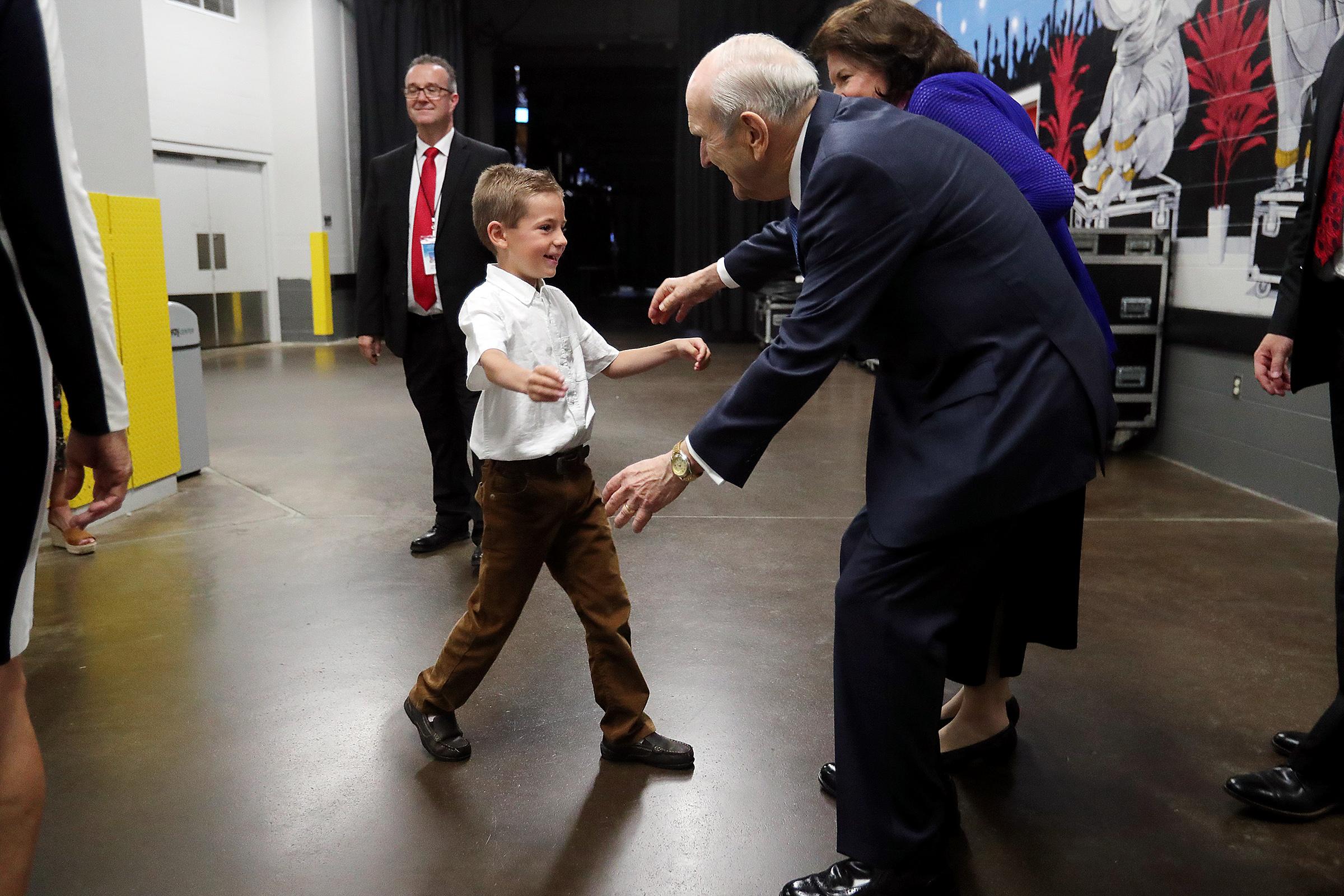 Eli Webster camina hacia su bisabuelo, el presidente Russell M. Nelson, antes del devocional del 9 de junio de 2019 en el Amway Center en Orlando, Florida.