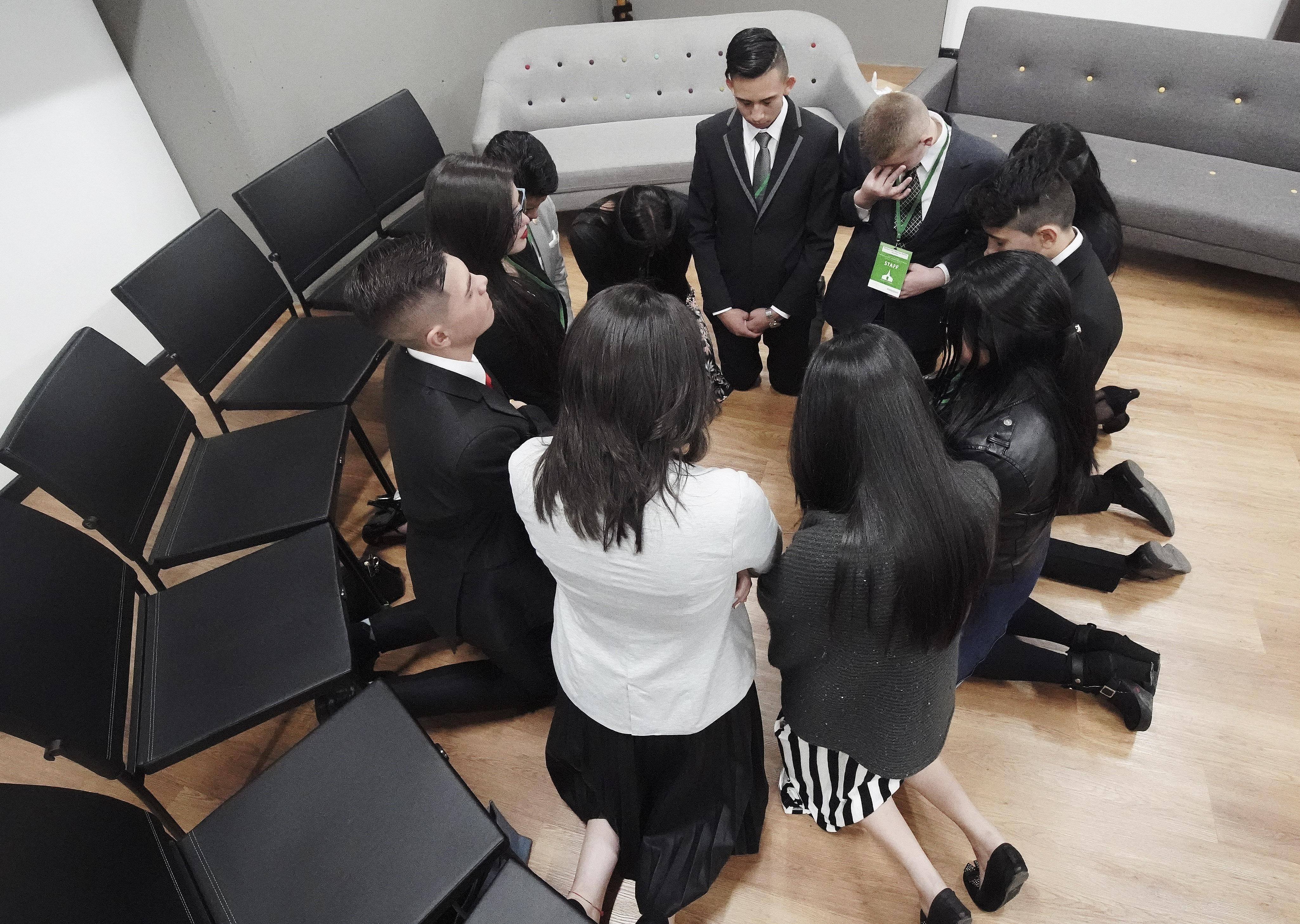 Los jóvenes asistentes oran antes de reunirse con el presidente Russell M. Nelson de La Iglesia de Jesucristo de los Santos de los Últimos Días en Bogotá, Colombia, el domingo 25 de agosto de 2019.