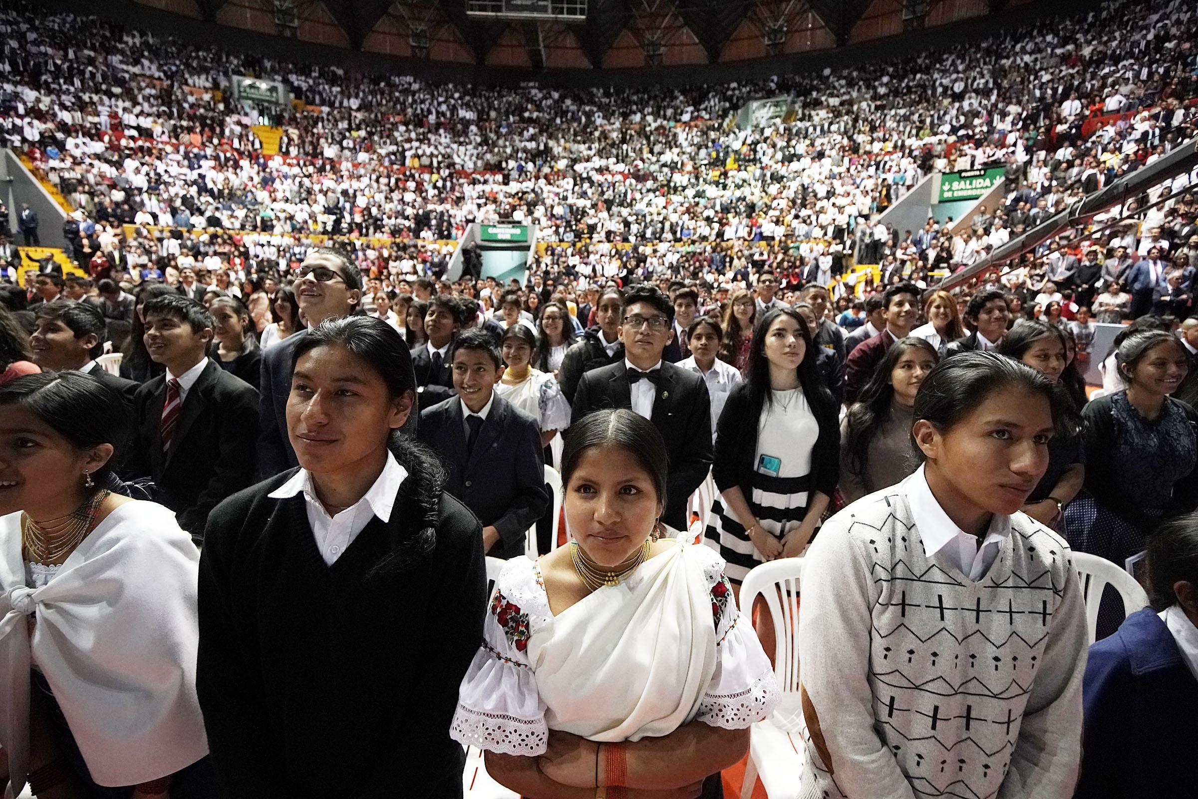 Los jóvenes en la audiencia se estiran a petición del presidente Russell M. Nelson de La Iglesia de Jesucristo de los Santos de los Últimos Días, durante un devocional de la gira ministerial latinoamericana en Quito, Ecuador, el lunes 26 de agosto de 2019. Al centro está Nahomi Campo.
