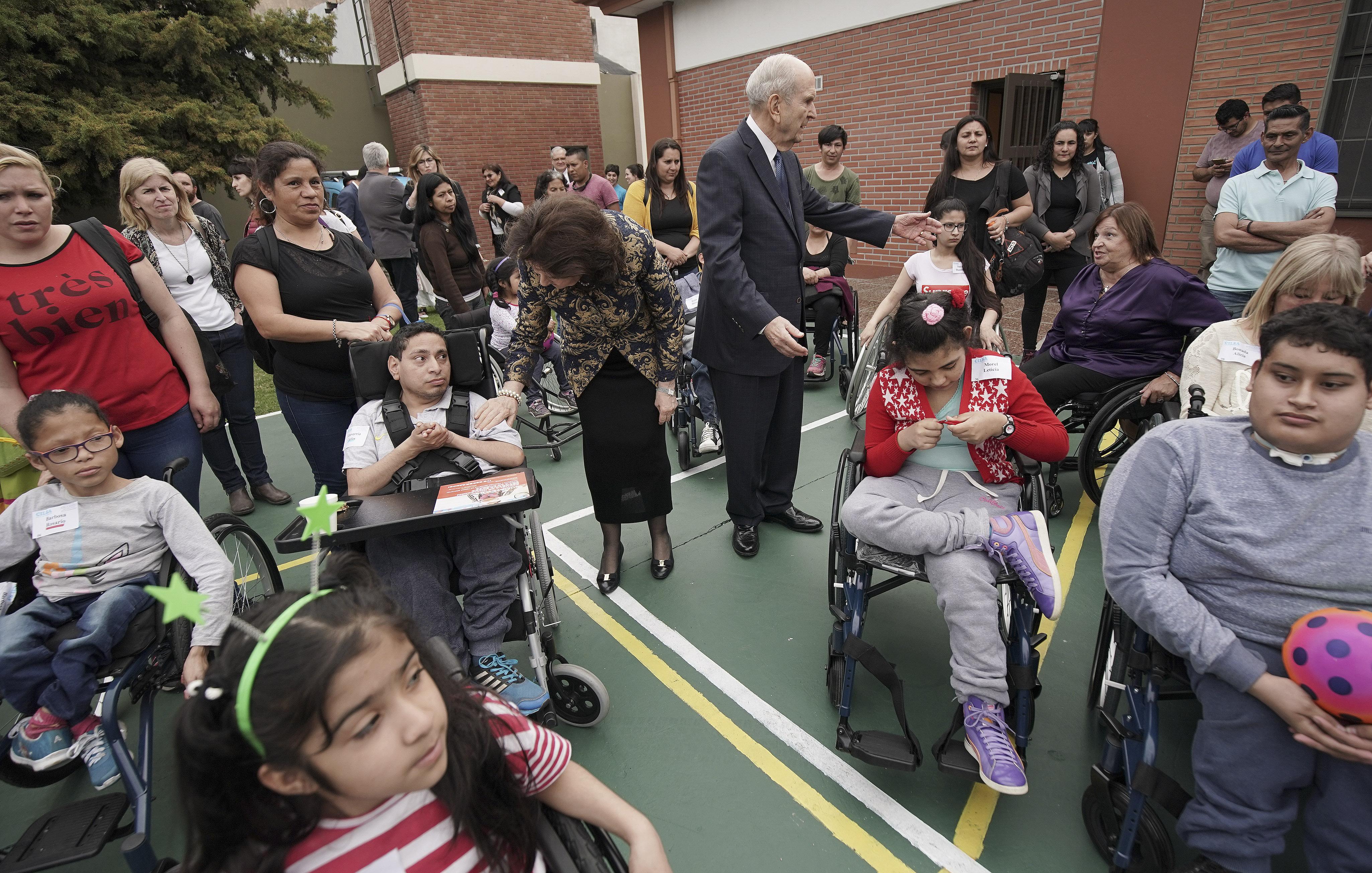 Presidente Russell M. Nelson, de La Iglesia de Jesucristo de los Santos de los Últimos Días, y su esposa, la hermana Wendy Nelson, se paran con los destinatarios después de que Latter-day Saint Charities donaron las sillas de ruedas en Buenos Aires, Argentina, el miércoles 28 de agosto de 2019.