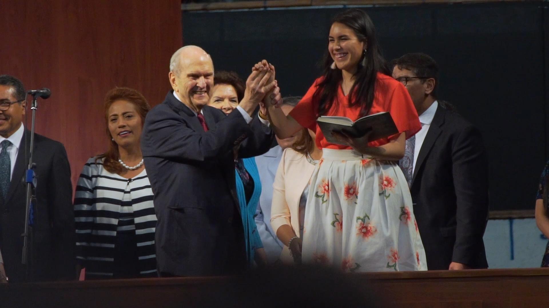 El presidente Russell M. Nelson, de La Iglesia de Jesucristo de los Santos de los Últimos Días, ayuda a Isabela Castellano mientras dirige una canción al final de un devocional de la gira ministerial latinoamericana en Quito, Ecuador, el lunes, 26 de agosto de 2019.