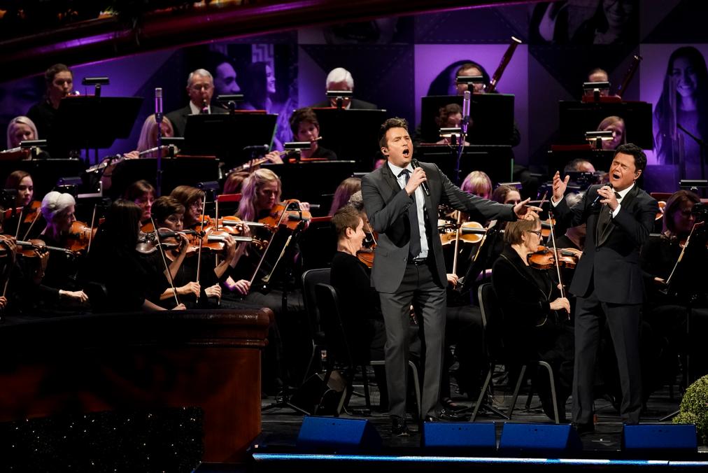 Nathan Pacheco, Donny Osmond, el Coro del Tabernáculo y la Orquesta de la Plaza del Templo se presentan durante una celebración del 95° cumpleaños del presidente Russell M. Nelson, de La Iglesia de Jesucristo de los Santos de los Últimos Días, en el Centro de Conferencias de Salt Lake City, el viernes, 6 de septiembre de 2019.