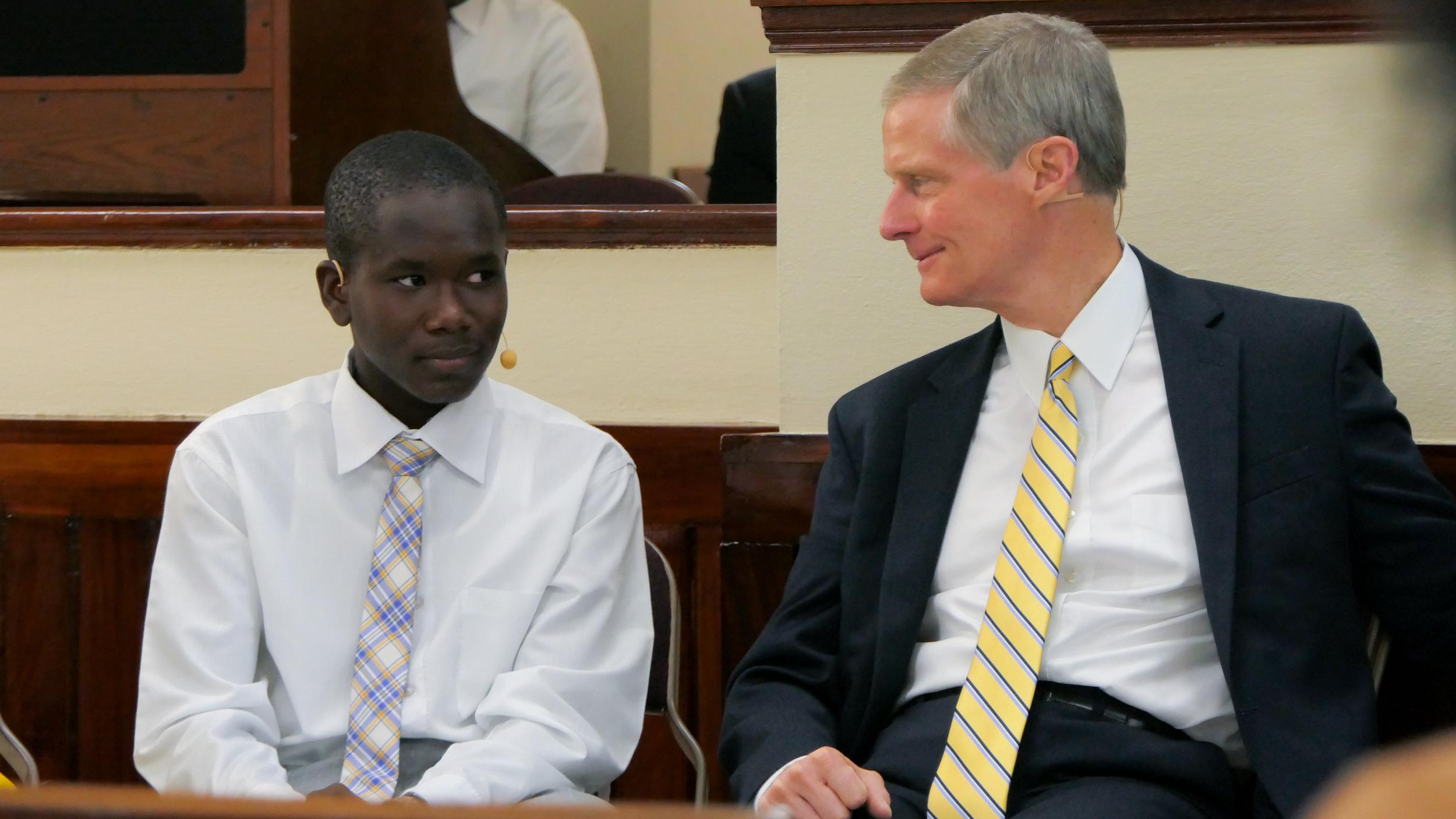 El élder David A. Bednar disfruta de charlar con un hombre joven durante el devocional para jóvenes del 31 de agosto de 2019 en Puerto Príncipe, Haití.