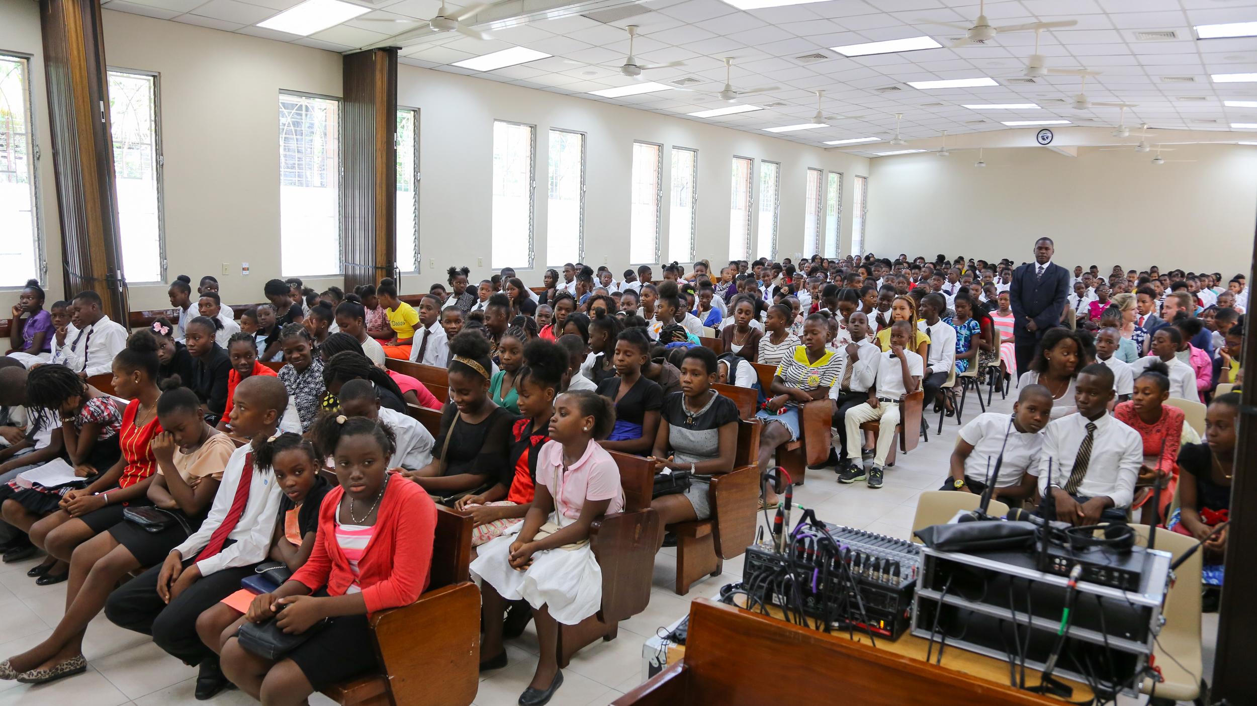 Cientos de jóvenes se amontonan en un centro de estaca de Puerto Príncipe, Haití, el 31 de agosto de 2019, previo al devocional para jóvenes en el que participó el élder David A. Bednar.