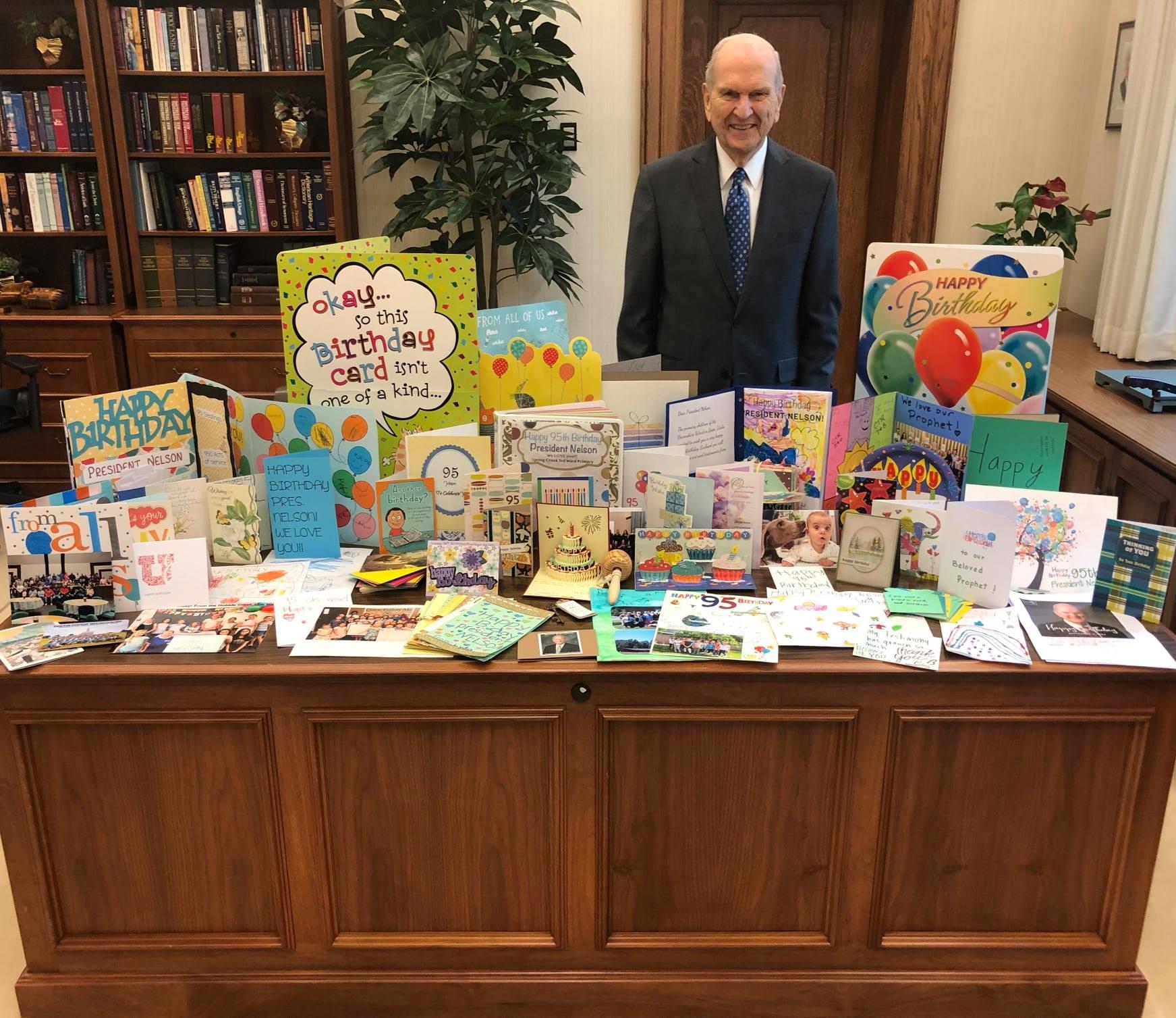 El presidente Russell M. Nelson de pie en frente de su escritorio lleno de tarjetas de cumpleaños y cartas de miembros y amigos de todo el mundo.