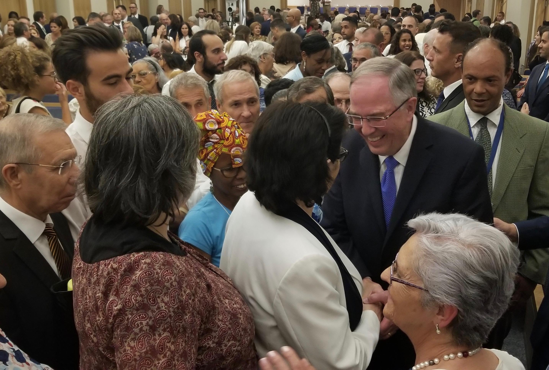 El élder Neil L. Andersen del Quórum de los Doce Apóstoles, derecha, saluda a una miembro luego de una reunión con los santos de los últimos días pioneros de Portugal el sábado, 14 de septiembre de 2019, en Lisboa.