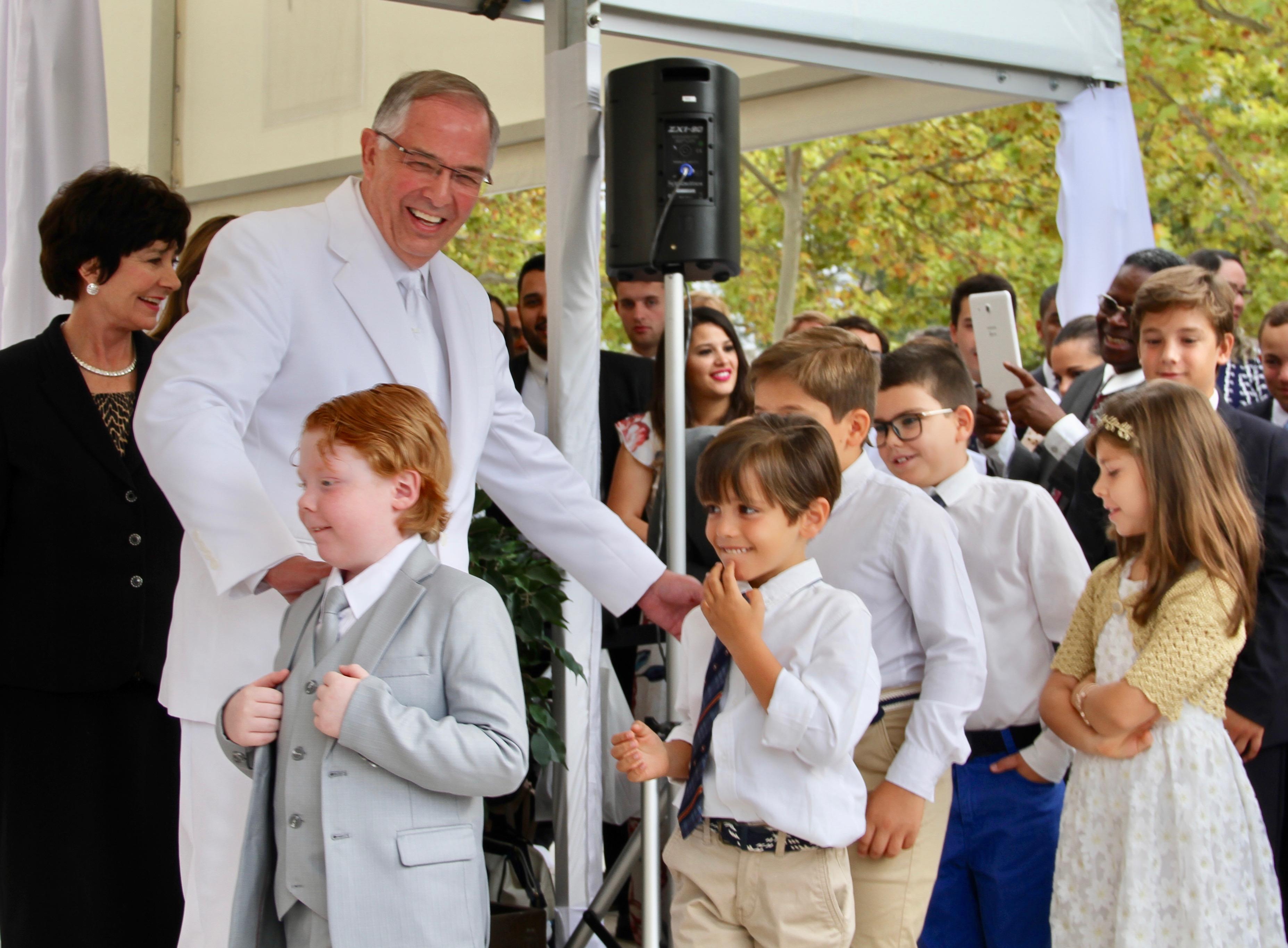 El élder Neil L. Andersen, del Quórum de los Doce Apóstoles, ayuda a varios niños para que participen en la ceremonia de coronación de la piedra angular de la dedicación del Templo de Lisboa Portugal, el domingo, 15 de septiembre de 2019.
