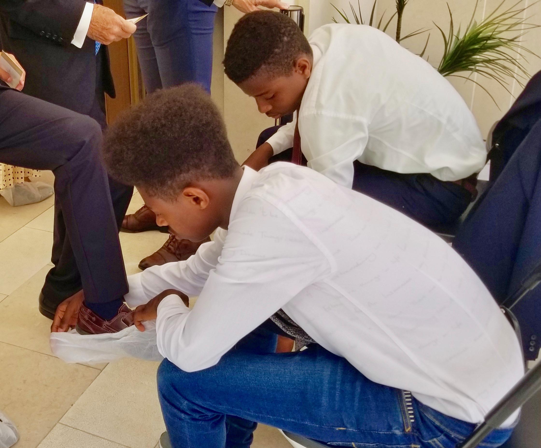 Hombres jóvenes ayudan a los asistentes a la dedicación del templo a ponerse los cobertores de zapatos fuera del Templo de Lisboa Portugal, el domingo, 15 de septiembre de 2019.
