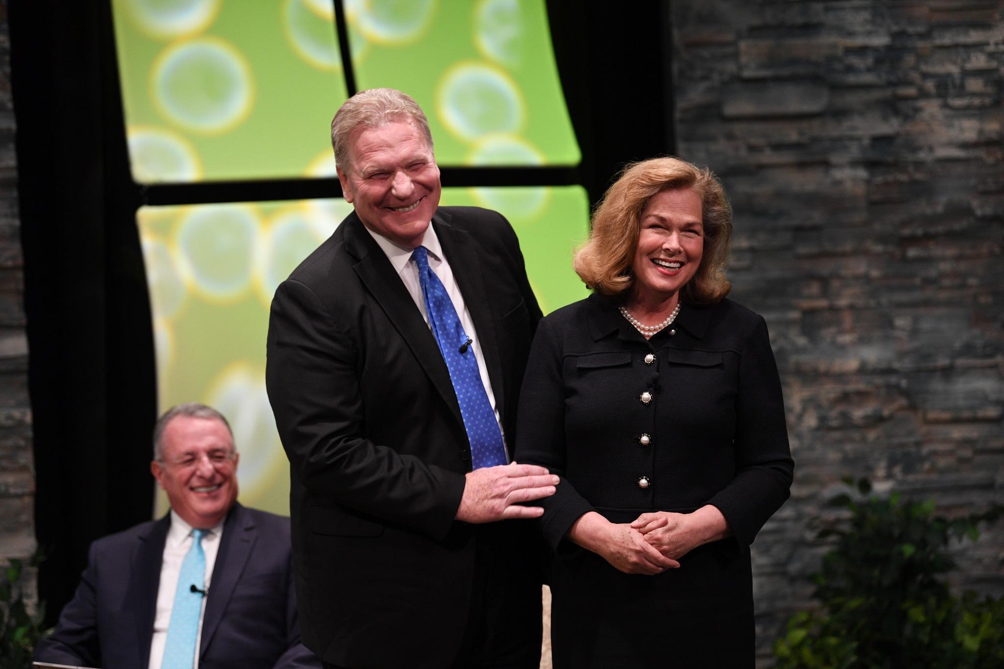 El élder Craig C. Christensen, de los Setenta, presenta a su esposa, Debbie, a la audiencia de jóvenes adultos en el Devocional Mundial Cara a Cara, el domingo, 15 de septiembre de 2019, en Provo, Utah.