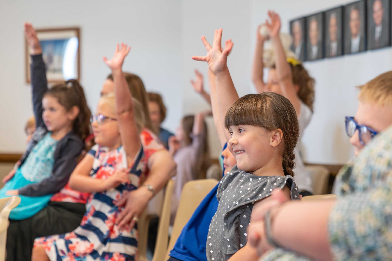 Niños de una estaca piloto en Columbus, Ohio, levantan su mano durante la Primaria. Aprender el Evangelio en la Iglesia y en el hogar es un componente clave del nuevo programa Niños y jóvenes.