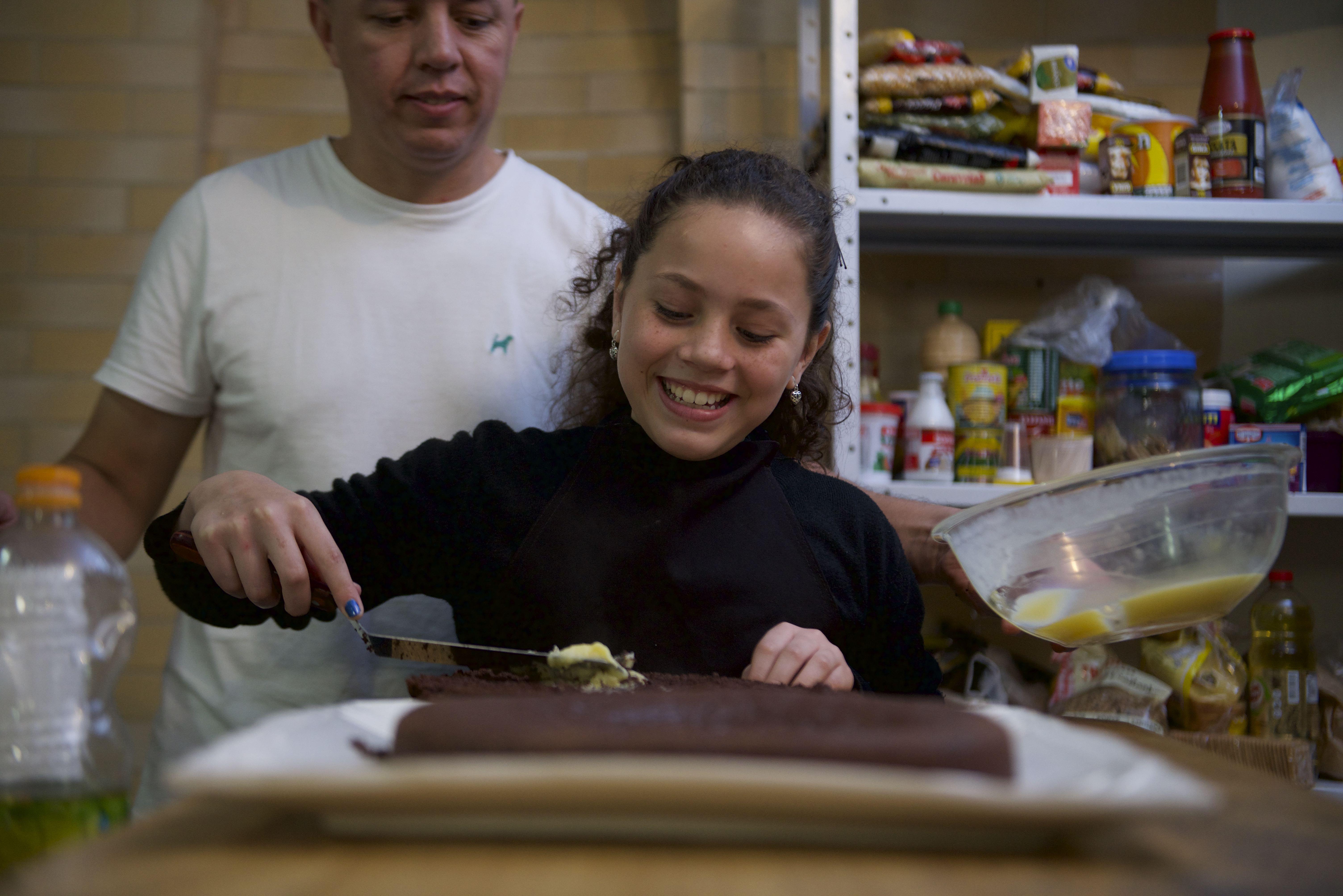 Fernanda, una niña de 10 años, de Curitiba, Brasil, hornea un pastel con su padre. Como parte del programa Niños y jóvenes, ella se puso la meta de aprender a cocinar.