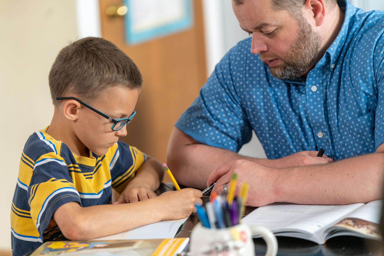 Peter, de 9 años, de una estaca piloto en Columbus, Ohio, practica la lectura y escritura con su padre. Como parte del programa Niños y jóvenes, Peter se puso la meta de pasar su examen de lectura en la escuela.