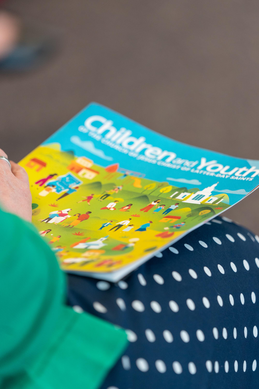 Un líder sostiene una copia de la Guía introductoria para padres y líderes del nuevo programa Niños y jóvenes. Copias de esta guía fueron distribuidas después de la presentación en video el domingo 29 de sept.