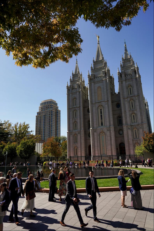 Personas caminan fuera de la Manzana del Templo antes de la sesión de sábado por la noche de la Conferencia General semi-anual 189 de La Iglesia de Jesucristo de los Santos de los Últimos Días, en Salt Lake City, el sábado 5 de octubre de 2019.
