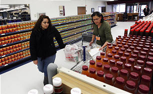 La hermana Tere Wilson, derecha, ayuda a una mujer con una orden de productos del almacén del obispo a recoger artículos en el Almacén del Obispo de la Manzana de Bienestar en Salt Lake City.