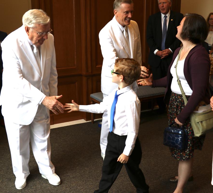 Presidente M. Russell Ballard despide a un jovencito después de la rededicación del Templo de Raleigh, Carolina del Norte el 13 de octubre de 2019. Élder Kevin R. Duncan, a la derecha, estrecha la mano de otra participante del templo.