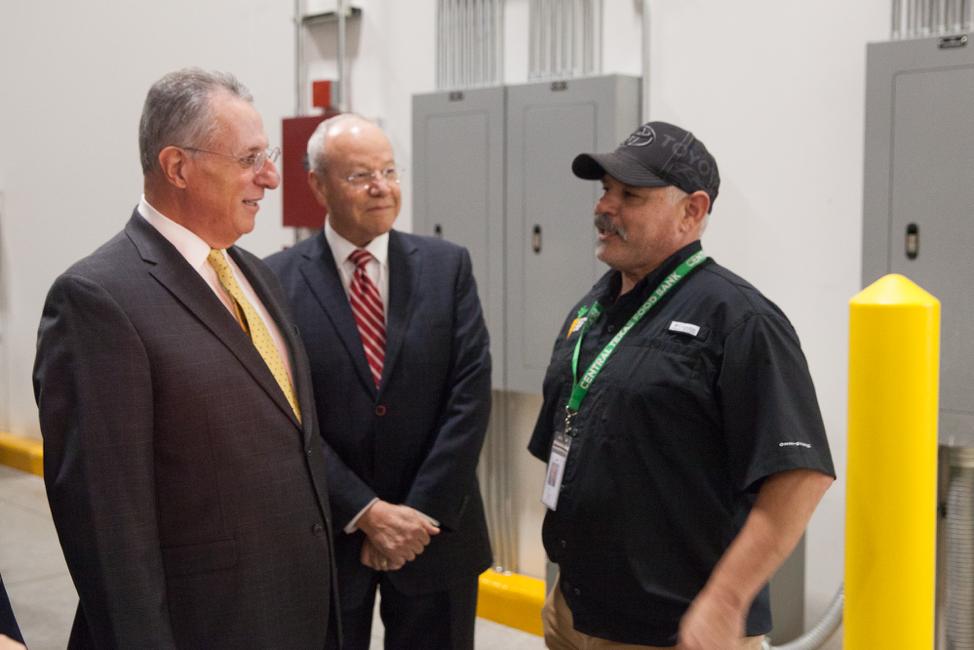 Élder Ulisses Soares habla con un empleado del Central Texas Food Bank durante una visita el 18 de oct. de 2019.